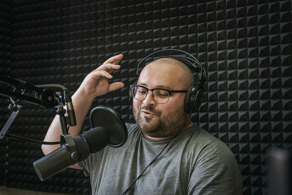 Smiling and gesturing radio host with headphones on his head reading news from paper into studio microphone on radio station